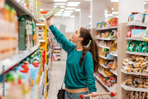 Fotografía A young pretty Caucasian woman with a grocery cart pulls a juice box from the top shelf