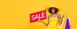 Surprised fashionable African American woman carrying shopping bags and red sale sign in isolated yellow banner background with copy space