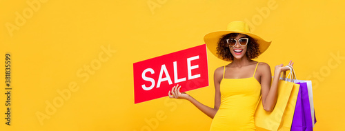 Fototapeta Surprised fashionable African American woman carrying shopping bags and red sale sign in isolated yellow banner background with copy space obraz