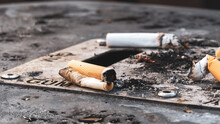 Focus On Cigarette Butts On An Outdoor Ashtray Bin