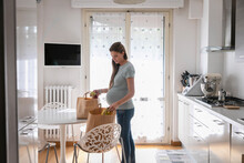 Pregnant Woman With Grocery In Paper Bags At Home