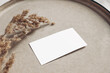 canvas print picture Closeup of blank business card mockup. Dry grass on beige ceramics plate. Fall and Thanksgiving concept. Autumn styled stock still life photo. Selective focus, no people.