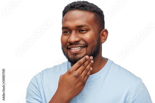 Fototapeta people, grooming and shaving concept - portrait of happy smiling young african american man touching his beard over white background obraz