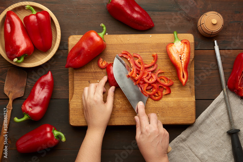 Leinwand Poster woman cuts red bell pepper into pieces on wooden board, brown wooden table