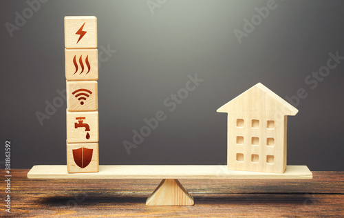 Fotografia House and blocks with utilities public service symbols on scales