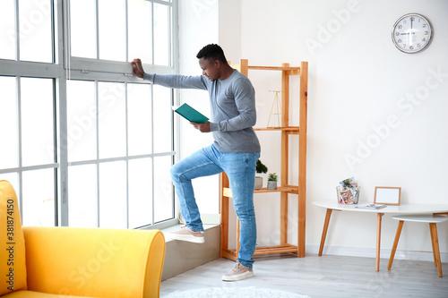 Fényképezés African-American man reading book at home