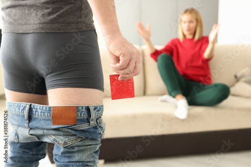 Fotografía Man stands with his pants down in his underpants and holds condom in front of woman sits and spreads his arms