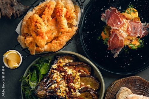 Fototapeta Delicious tapas selection composed of deep fried calamaris, grilled eggplant and cured ham with eggs obraz