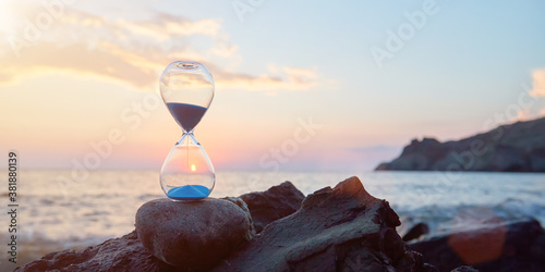 Fotografie, Obraz Hourglass with blue falling sand inside