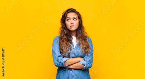 Fotografering doubting or thinking, biting lip and feeling insecure and nervous, looking to c
