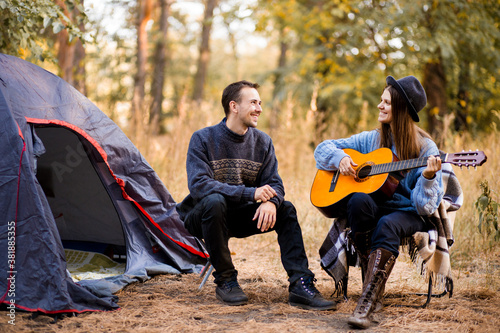 Cuadros en Lienzo Portrait of young couple sitting on camp chair with guitar near camp tent