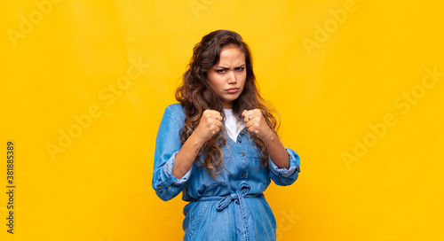 Fotografía looking confident, angry, strong and aggressive, with fists ready to fight in b