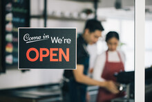 A Business Sign That Says 'Come In We're Open' On Cafe And Coffee Shop Or Restaurant Window. Vintage Tone
