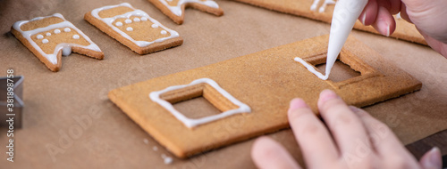 Young woman is decorating Christmas Gingerbread House cookies biscuit at home with frosting topping in icing bag, close up, lifestyle Canvas