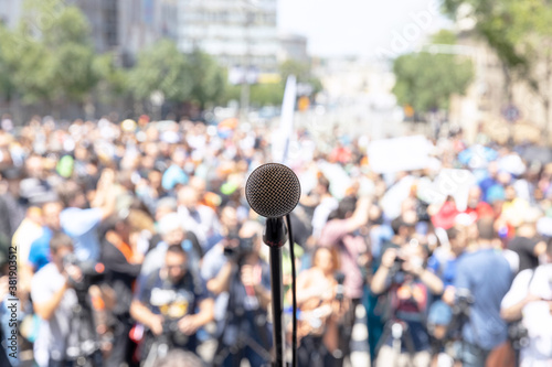 Focus on microphone, blurred group of people at mass protest in the background Wallpaper Mural