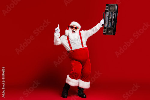 Full length body size view of his he attractive cheerful Santa having fun dancing carrying retro cassette tape player isolated bright vivid shine vibrant red burgundy maroon color background