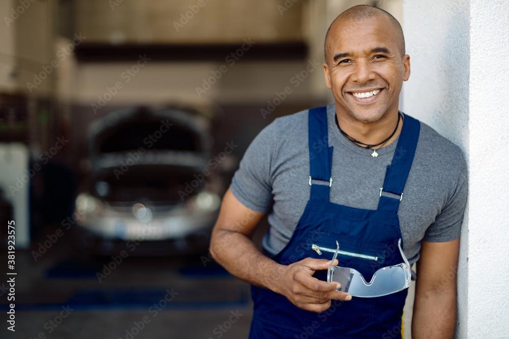 Fototapeta Happy African American auto mechanic in a repair shop.