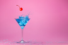 Red Cherry Falling Into A Blue Coktail Splashing In Martini Cup Isolated On Wet Pink Background With Space For Text. Concept Image For Entertainment Club And Party.