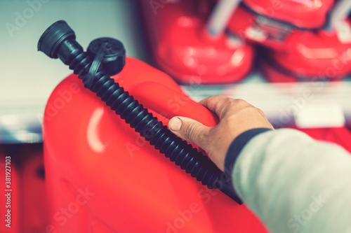 Fotografie, Obraz Red canister in the hands of a man