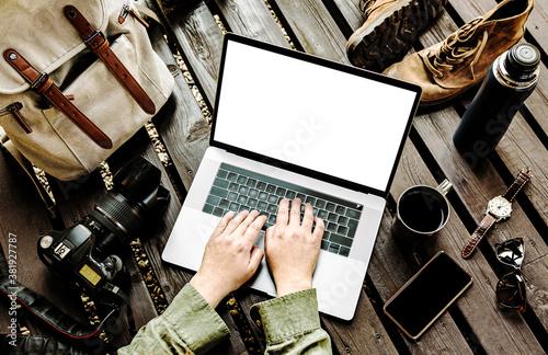Traveler or travel photographer working on laptop among his equipment Wallpaper Mural