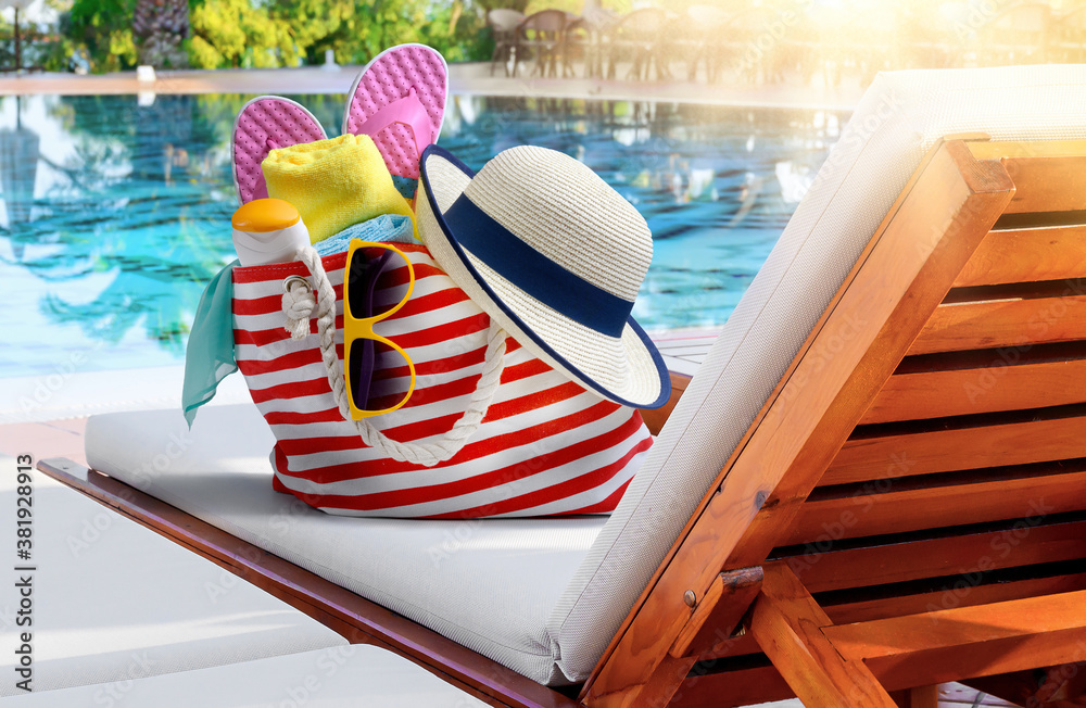 Fototapeta Beach bag with accessories on sun lounger near swimming pool in luxury resort