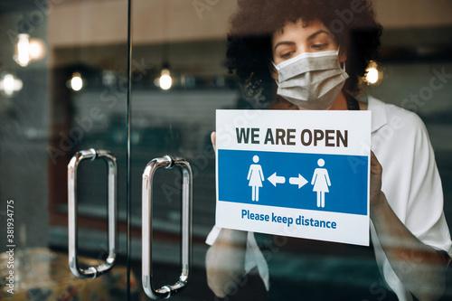 Fotografie, Obraz Restaurant female owner with protective face mask, reopens after lockdown quarantine