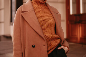 Young woman  with cropped head in the orange knitted cozy sweater and brown coat standing on the street. Outdoor portrait in daylight. Autumn colours.