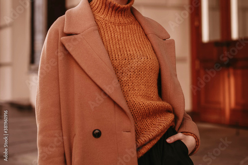 Fototapeta Young woman  with cropped head in the orange knitted cozy sweater and brown coat standing on the street