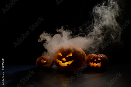 Valokuva Three creepy halloween steaming pumpkins with a carved luminous smirk on a black background