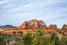 Juniper Trees And A Formation Of  Huge Red Sandstone Rocks  Under A Buttermilk Sky, Outside The City Of Sedona, Arizona