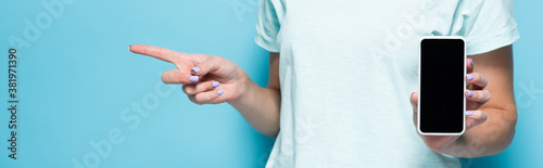 Fototapeta cropped view of young woman holding smartphone with blank screen and pointing aside on blue background, panoramic shot obraz