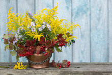 Autumn Bouquet Of Flowers With Viburnum Berries In A Copper Planter Outdoors