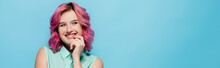 Young Woman With Pink Hair Smiling And Flirting Isolated On Blue, Panoramic Shot