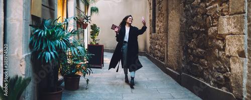 Fotografia Carefree Caucasian vlogger enjoying walking sightseeing around ancient streets u
