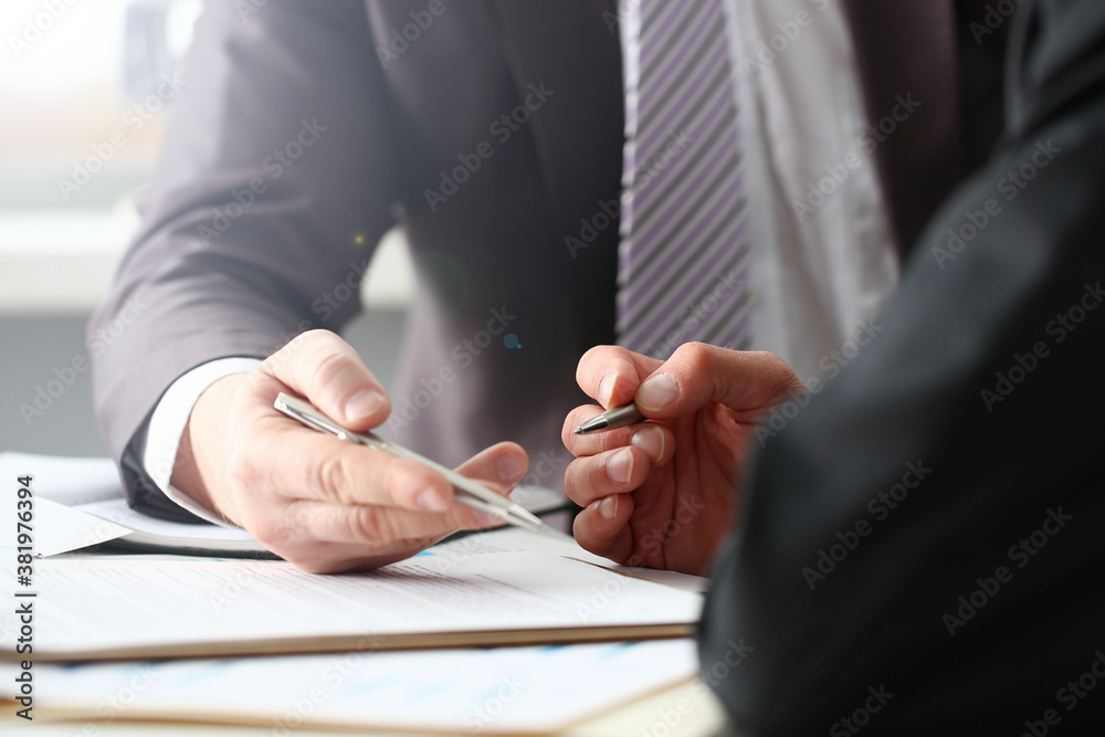 Fototapeta Male arm in suit and tie fill form clipped pad with silver pen closeup. Sign gesture read pact sale agent bank job make note loan credit mortgage investment finance executive chief legal teamwork law