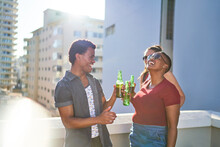 Happy Young Friends Drinking Beer On Sunny Urban Rooftop Balcony