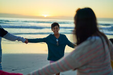 Happy Family Holding Hands In Circle On Ocean Beach At Sunset