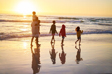 Family Walking In Ocean Surf O...