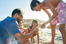 Family Playing On Sunny Beach