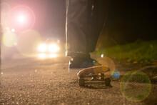Young Man Skateboarding In Headlights On Roadside