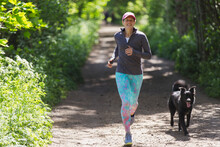Woman Jogging With Dog On Sunny Trail
