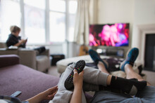 POV Family With Remote Control Watching TV In Living Room