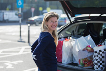 Portrait Happy Woman With Grocery Bags At Bag Of Car