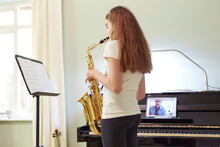 Girl Taking Online Saxophone Lesson At Home