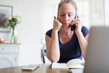 Woman Working From Home Talking On Telephone