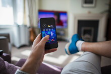 POV Man Adjust Temperature Control On Smart Phone In Living Room