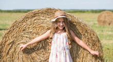 Cute Smiling Little Girl With Hat Posing In Front Of Wheat Straw Bale