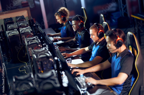 Team of professional cybersport gamers wearing headphones participating in eSpor Canvas