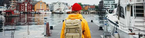 Obraz Man tourist with touristic rucksack wearing yellow jacket walking among authentic fishing boats. Wide image - fototapety do salonu