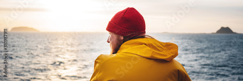 Obraz Wide image. Alone man traveling on ship and looking at sunset sea and foggy mountain on skyline. Hipster traveler wearing yellow raincoat and red hat enjoying beautiful ocean after storm - fototapety do salonu